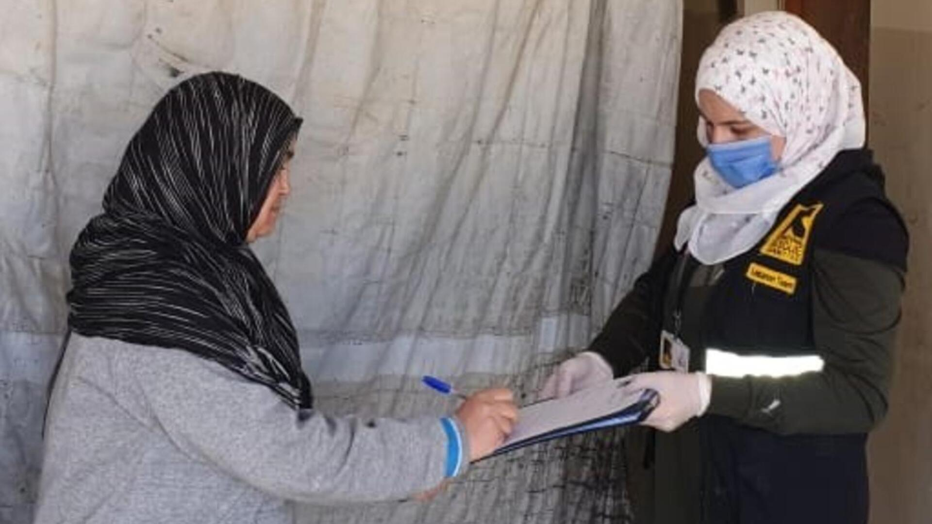 A Syrian refugee woman in Labanon signs a form to get cash assistance presented by an IRC staff member wearing PPE.