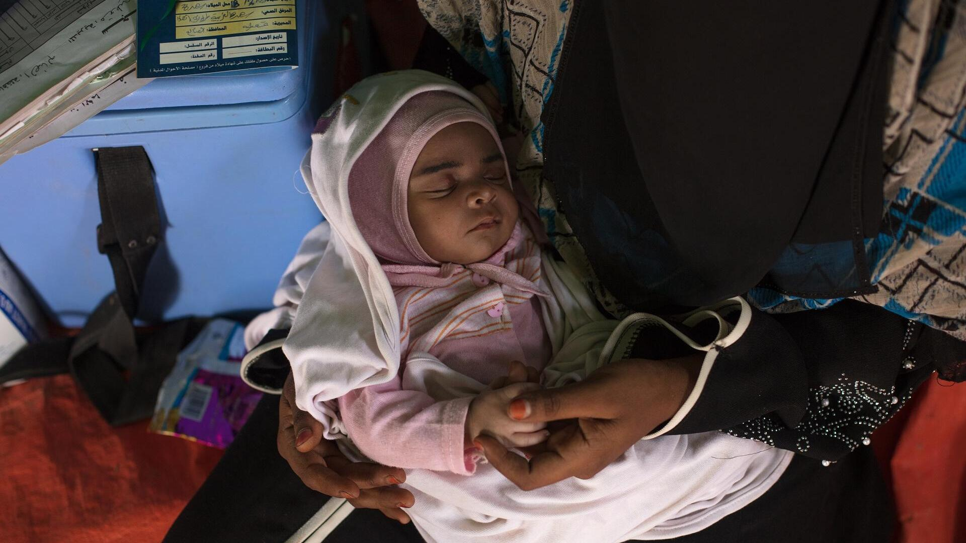 "Baby Enqath, or ""Rescue,"" sleeps in her mother's arms"