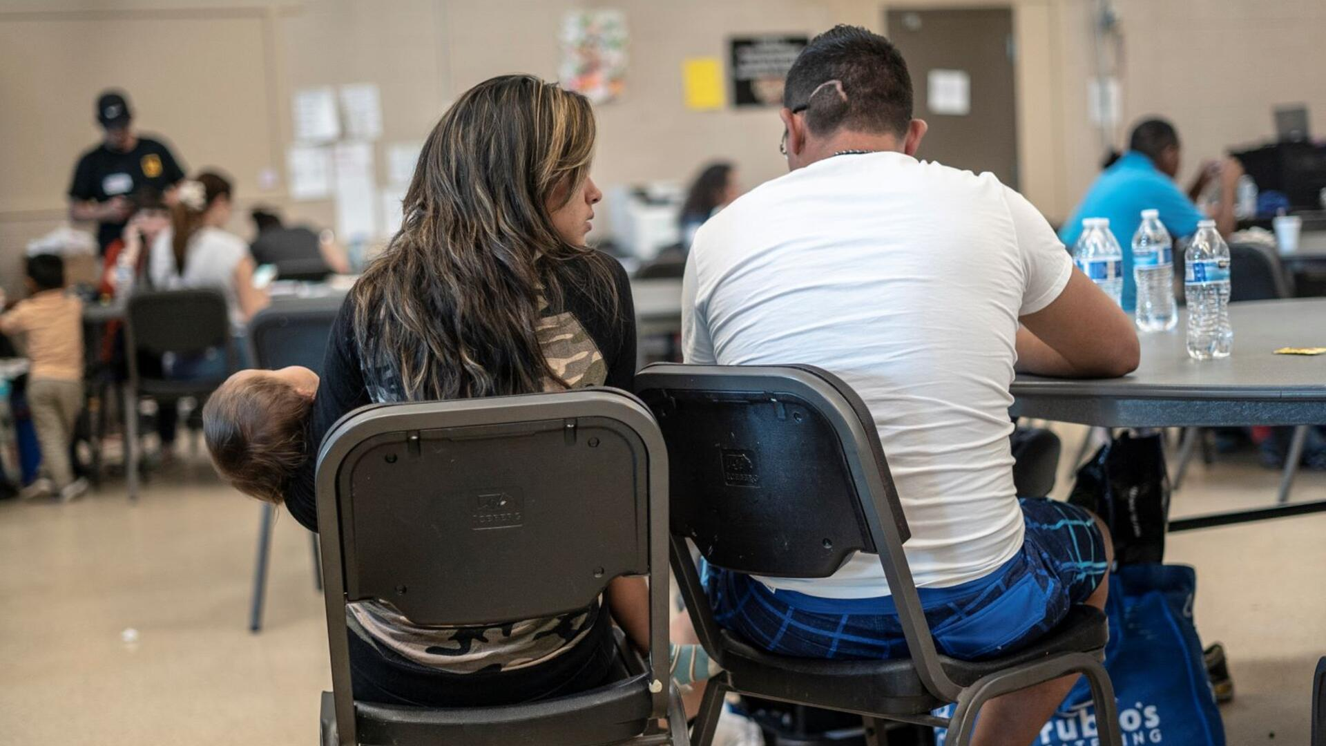 In the IRC's Welcome Center for asylum seekers, a husband and wife sit with their back to the camera as they discuss their journey as asylum seekers. The wife is holding their 2-year-old daughter.