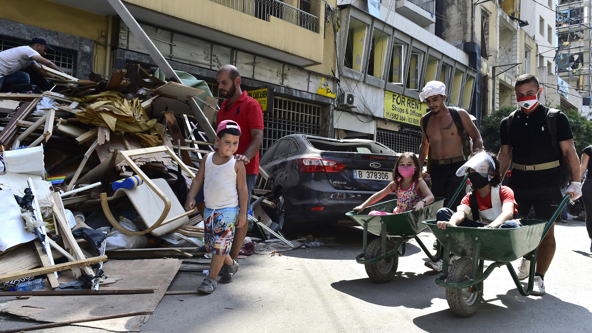 Two men push children in wheelbarrows past damage from the Aug 4, 2020 explosion in Beirut, Lebanon. Getty photo