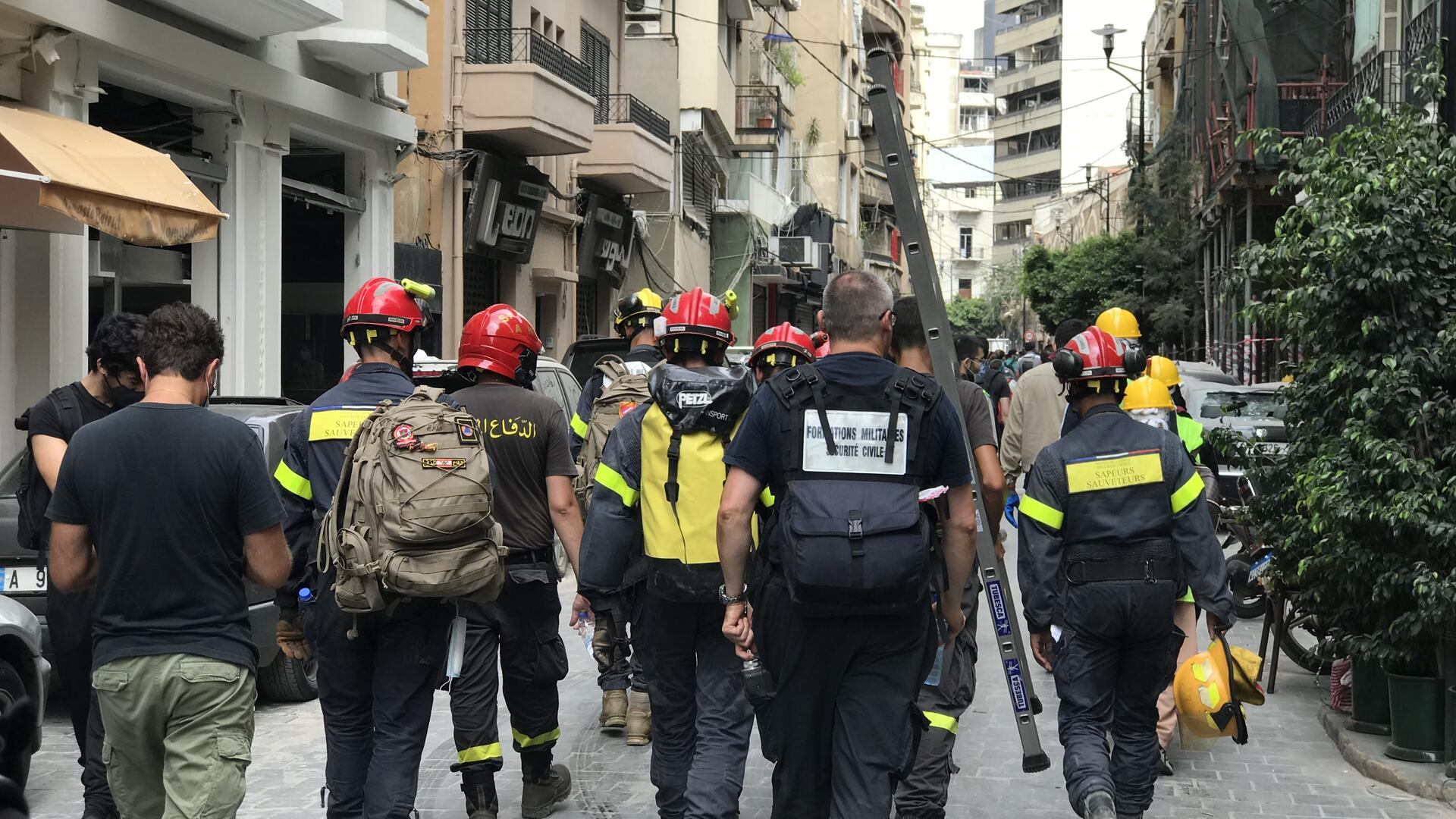 Firefighters walk down a street in Beirut, Lebanon after the Aug. 4 explosion