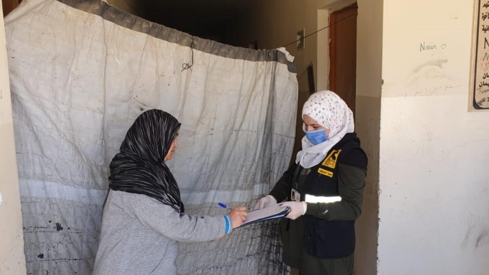 A woman signs a form offered by a female IRC aid worker wearing a mask as a COVID-19 precaution while distributing emergency cash assistance.