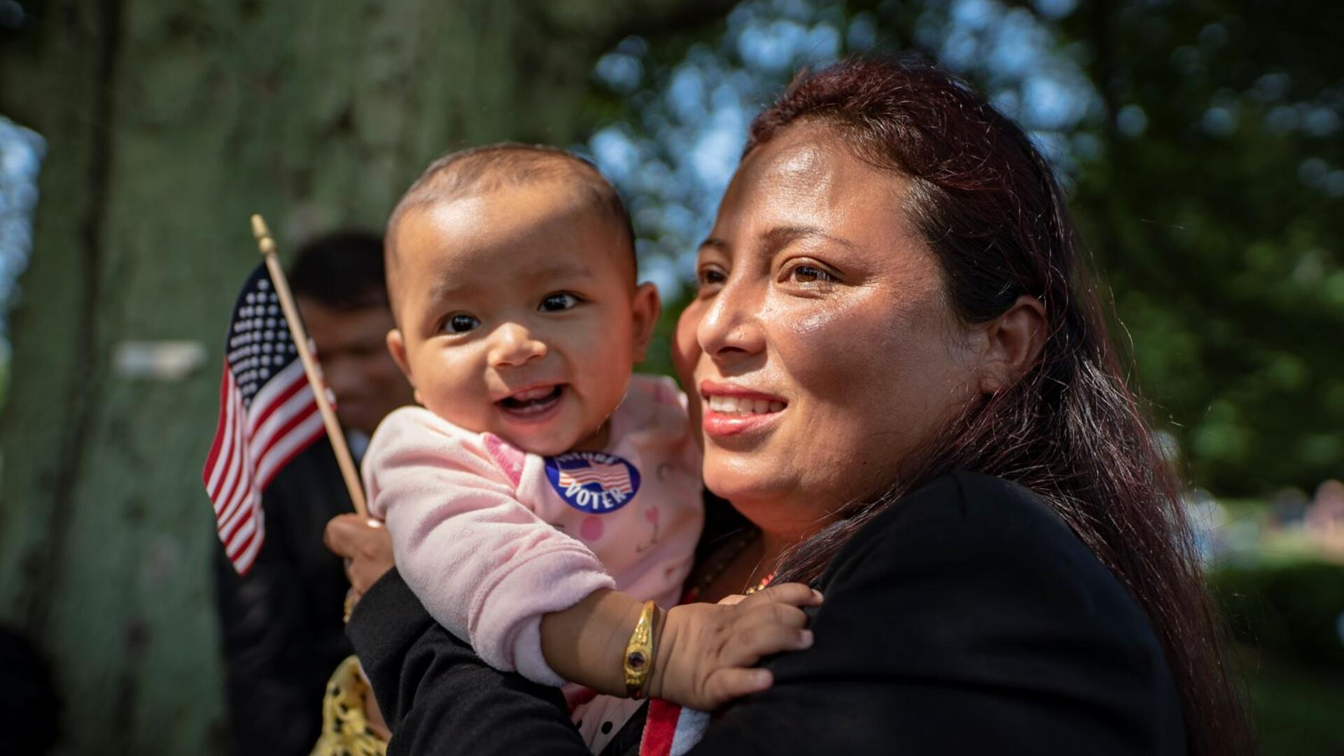 A newly naturalized citizen at a citizenship ceremony holds her baby and a small American flag. Both are smiling.