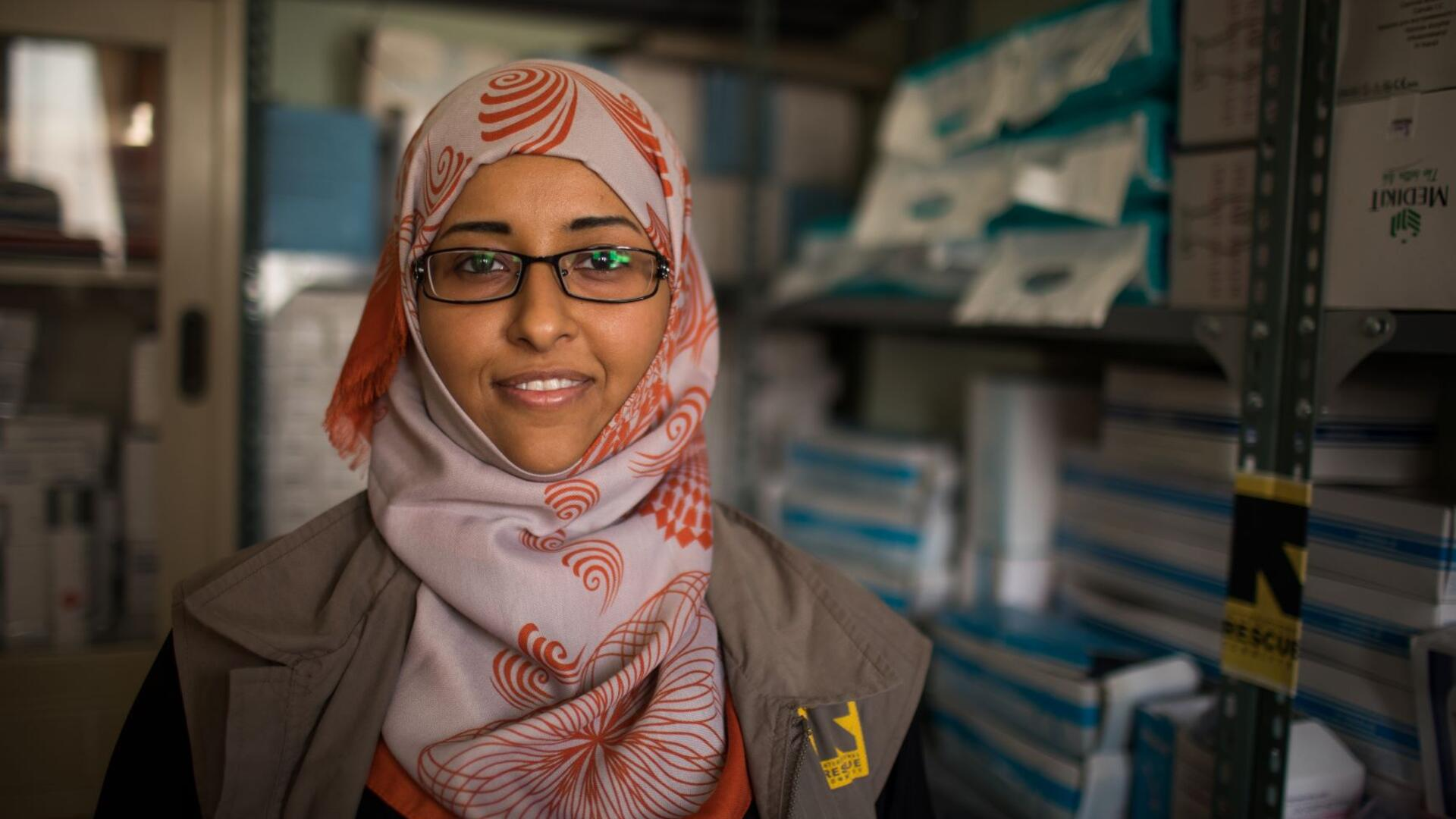 Dr. Rasha Rashed, a doctor and reproductive health manager for the IRC in Yemen, stands in a room with media supplies. She is wearing a red and white scarf and an IRC-branded vest.