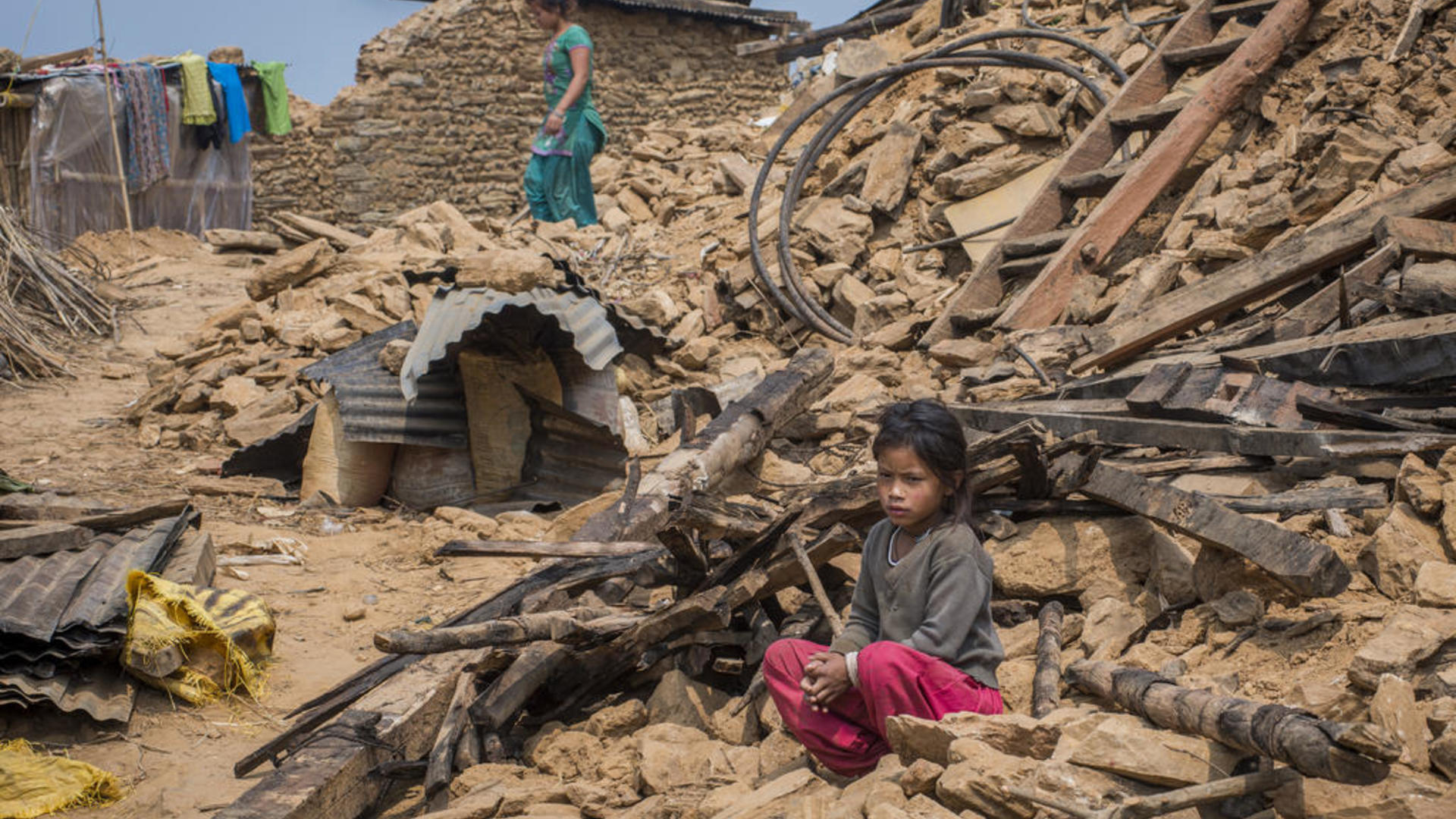 child sits in earthquake rubble in Nepal