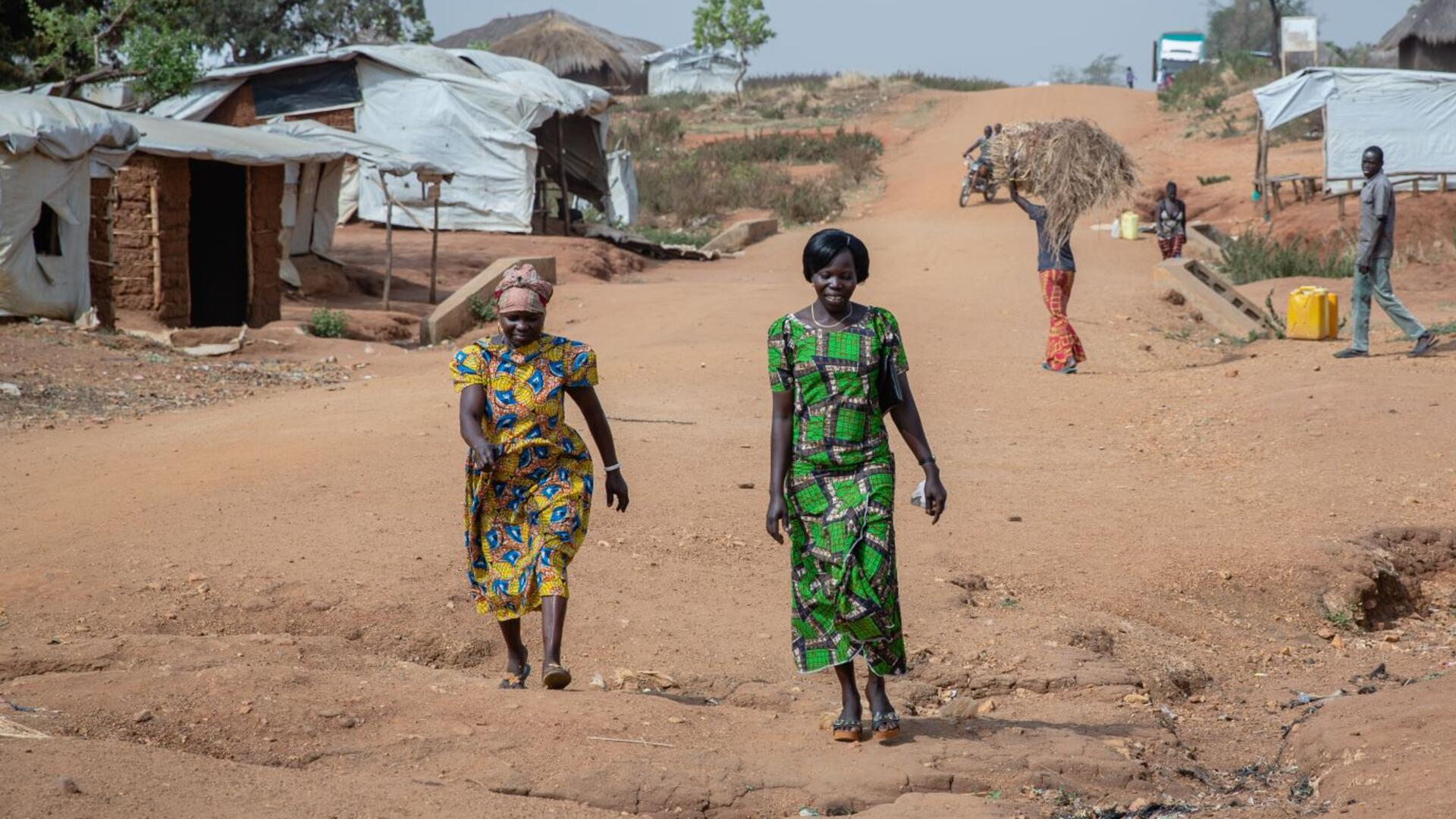 Women's rights activists Foni Grace and Loyce Tabu walk in Bidi Bidi refugeee settlement in Uganda.They are at the forefront of the photo and there are small makeshift homes and a man carrying a bale of hay behind them.