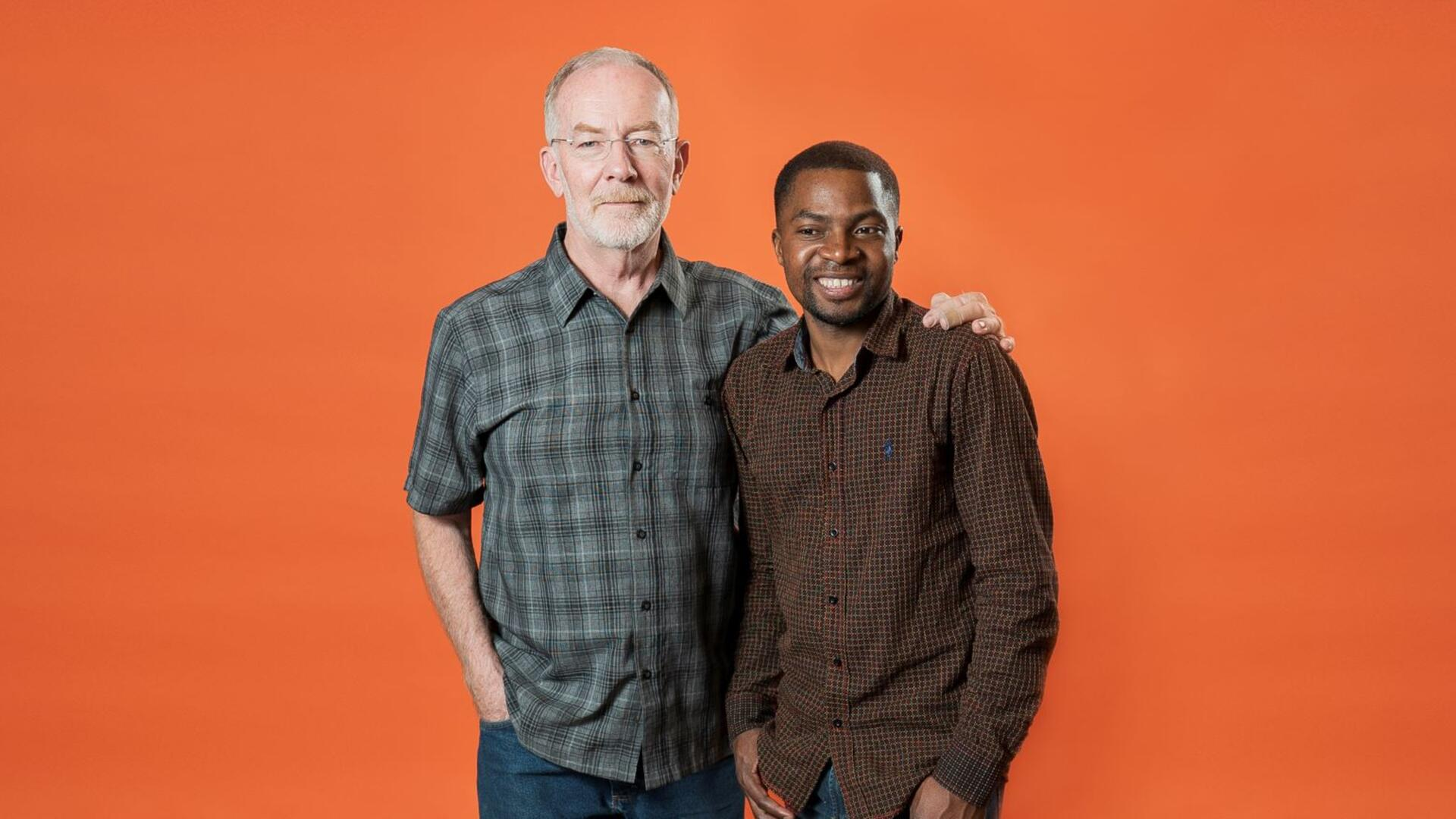 Robert Sebatware and Dave Kurz posing for the camera in front of an orange background.