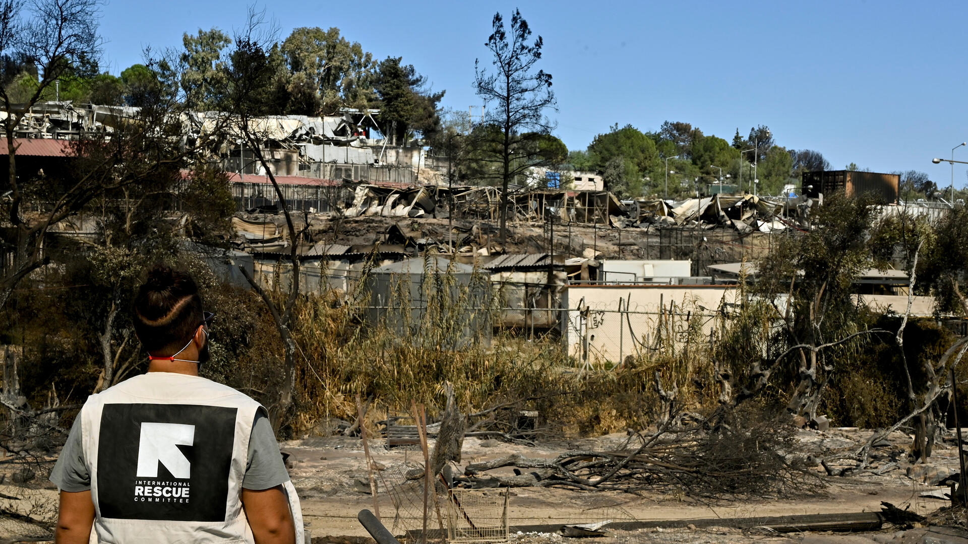 An IRC staff member views the burnt-out Moria refrugee camp in Lesbos, Greece