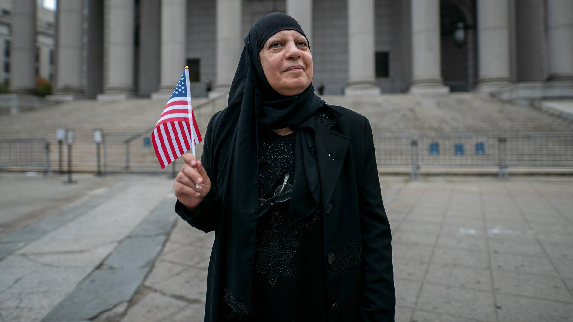 Maha al-Obaidi stands in front of a government building holding an American flag.