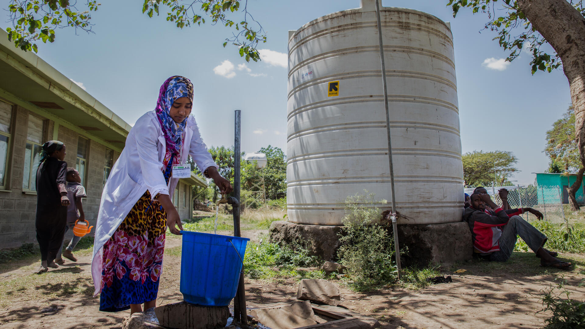An IRC staff member fills a bucket at a water point in Ethiopia