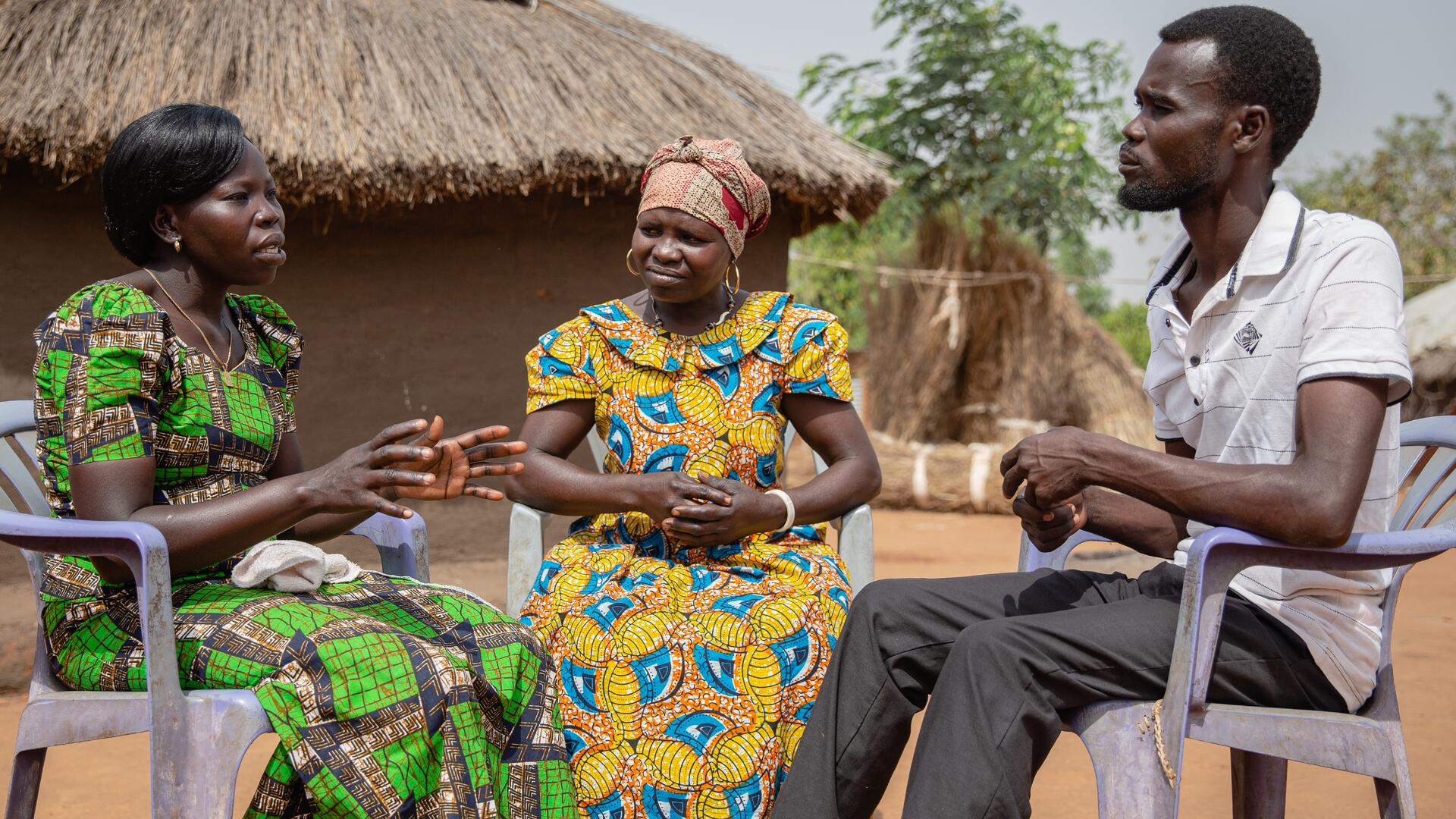 Two members of a women's group sit on plastic chairs outside a house in a Uganda refugee settlement speaking with a man about women's rights