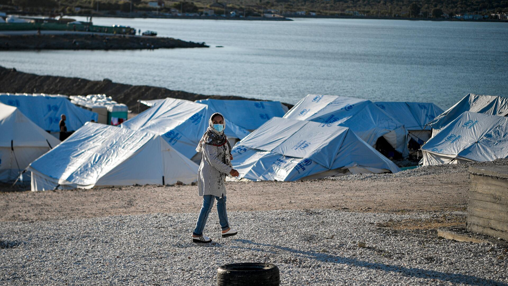 Rahima walks past tents in the refugee camp her family was relocated to on the Greek island of Lesbos.