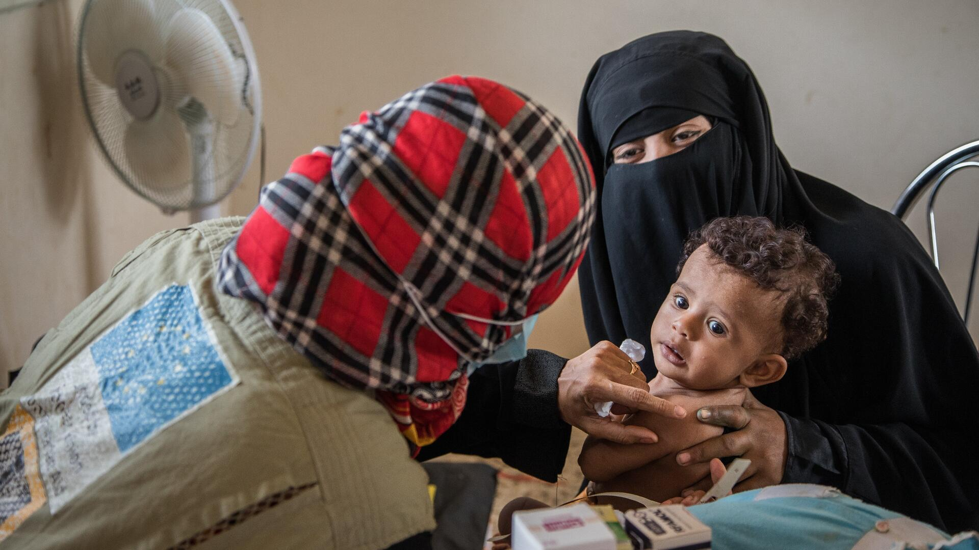 An IRC health worker examines a child in Yemen for malnutrition as his mother holds him in her arms.