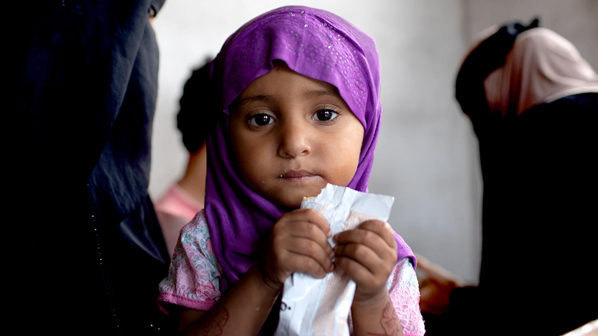 A young girl in Yemen being treated for acute malnutrition eats a peanut butter based nutritional paste.