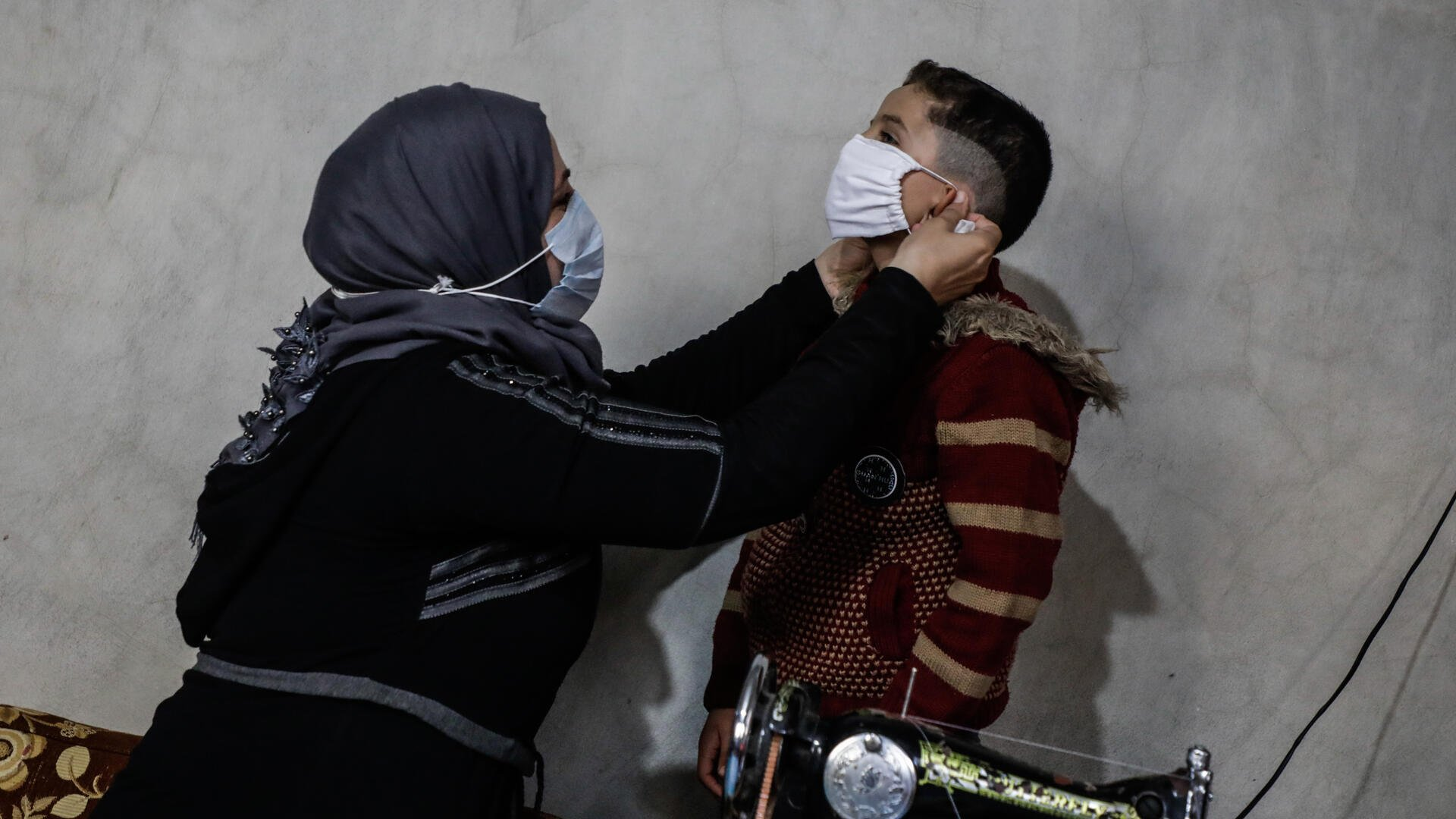 Um Abdo fits a COVID-19 face mask she's sewn on her son.