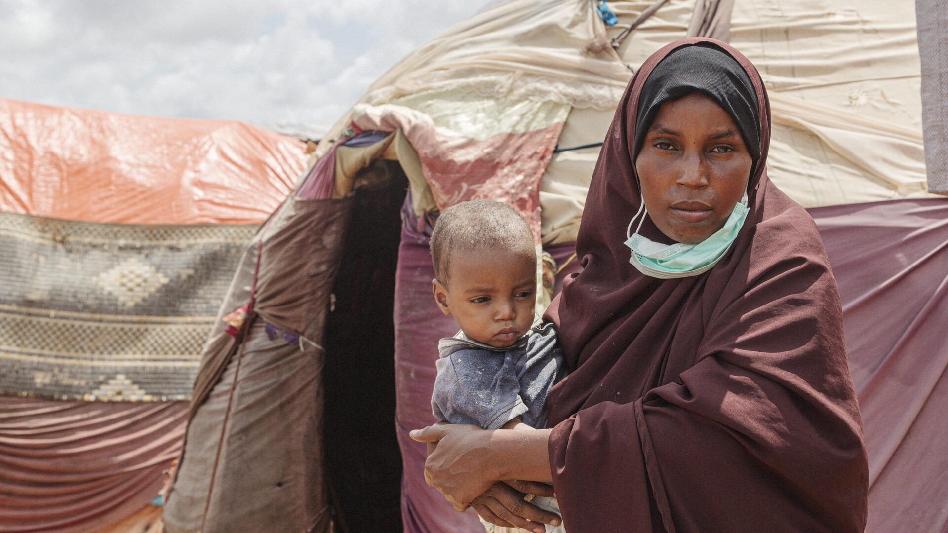 Amina holds her son while standing in front of several tents.