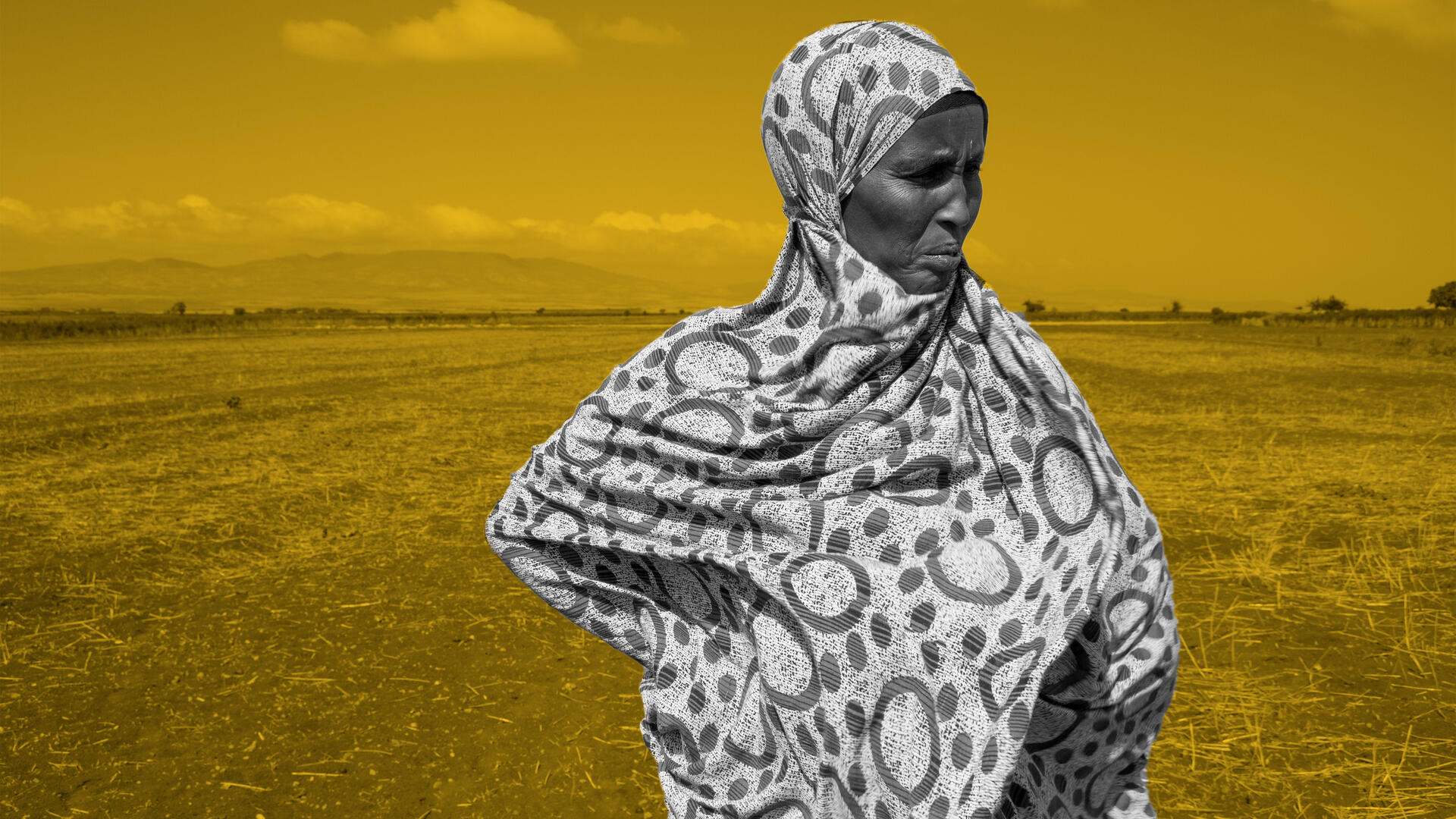 An elderly woman in Ethiopia stands in a dry field, hands at her hips.