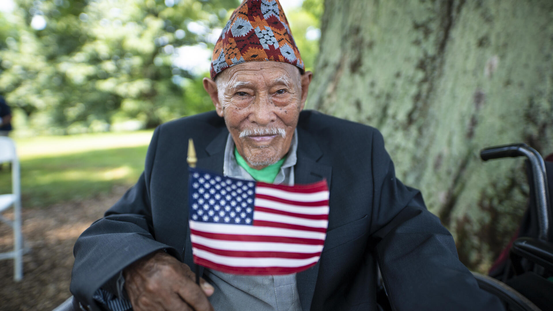 A seated refugee man holds a flag at a citizenship ceremony in Virginia