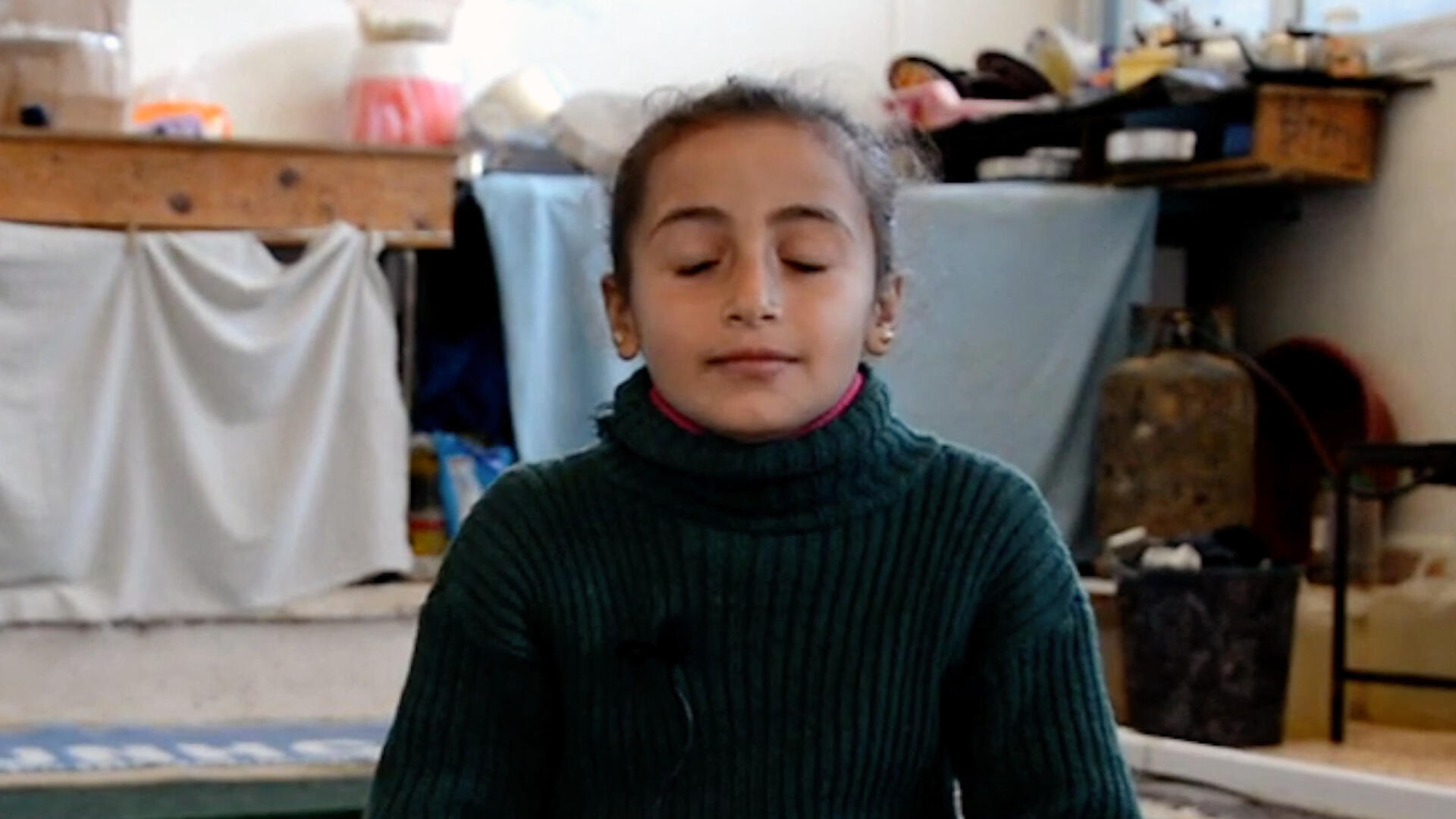 Eyes closed, Reem an 8-year-old girl in Syria, takes a deep breath while practicing mindfulness.