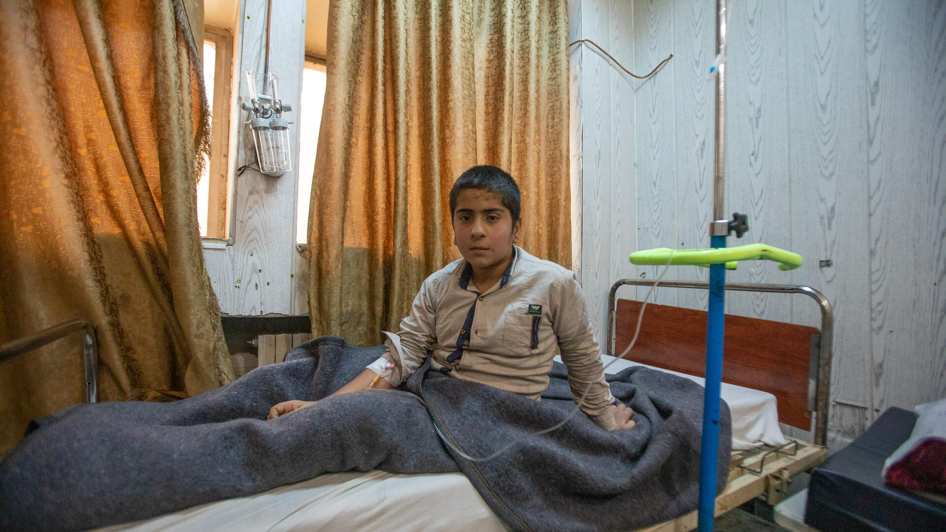 A patient sits up in his hospital bed in Syria.