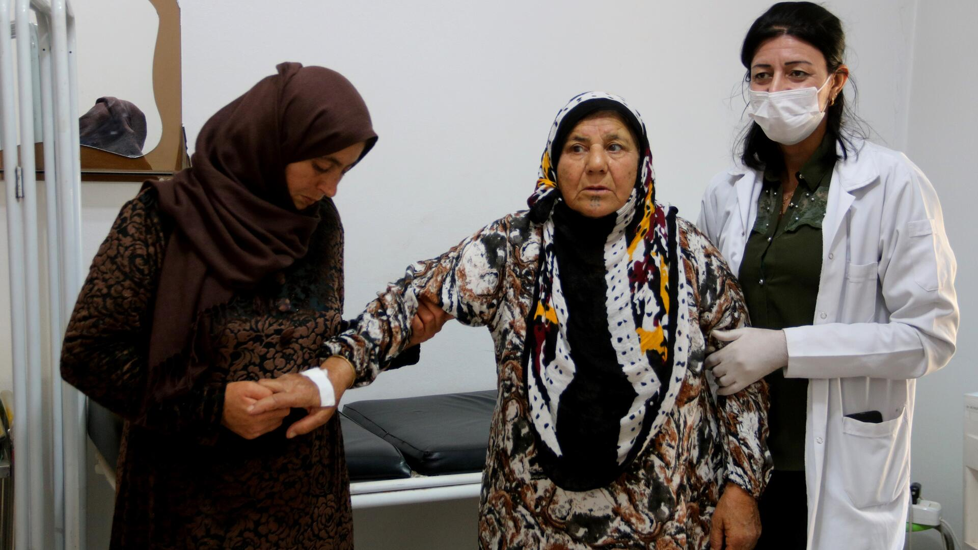 An elderly woman is assisted by a doctor and a relative in a health facility in Syria.
