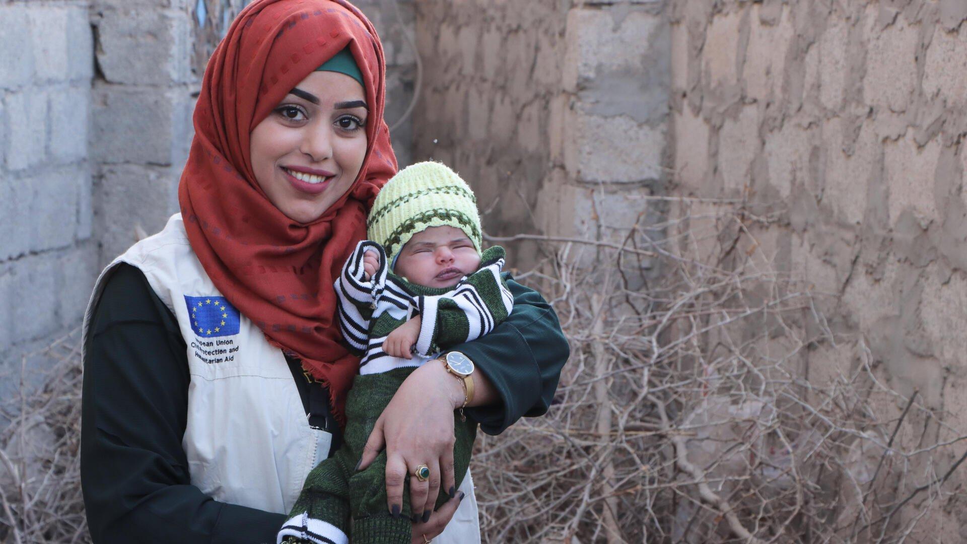 Dr. Bushra holds a baby in Yemen