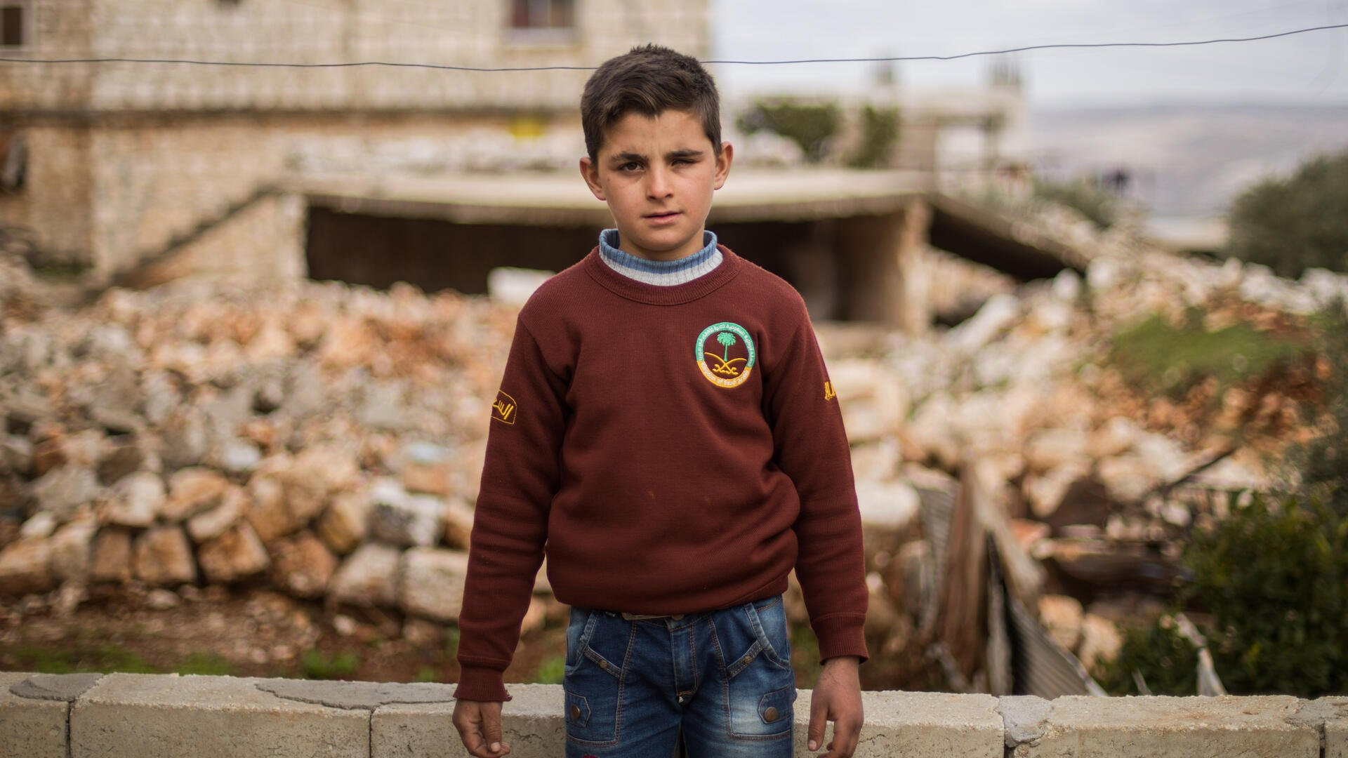 Ten-year-old Ali stands in front of his family's home which was damaged by an airstrike.