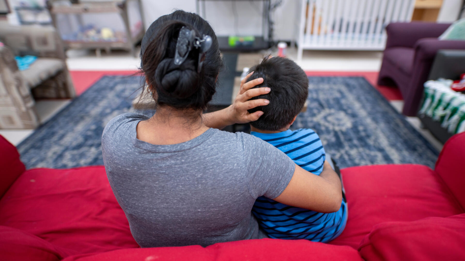 Angelina, an asylum seeker from Guatemala, sits on a red couch with her arms around her son at an IRC Welcome Center in Arizona.