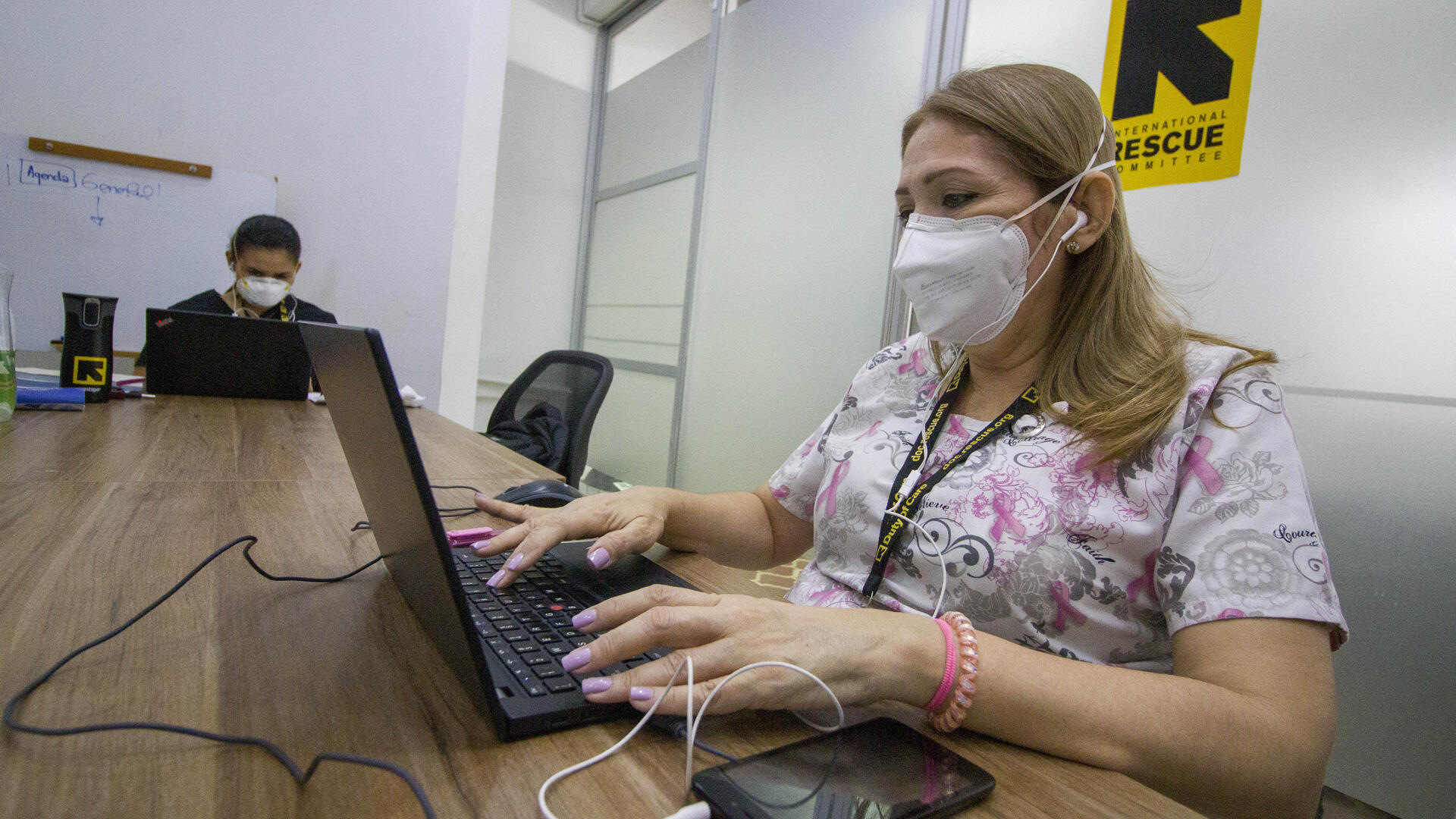 An IRC healthworker wearing a mask to protect herself from COVID-19 types at a laptop