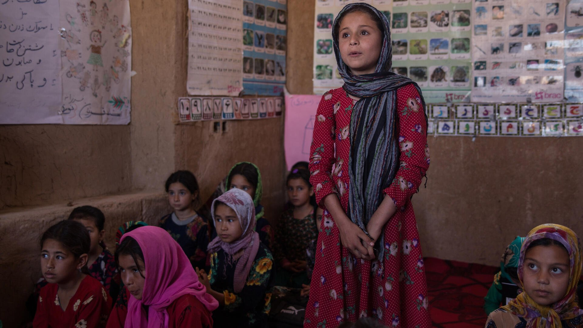 A girl surrounded by her classmates stands up to speak while clasping her hands in an IRC safe healing and learning space in Afghanistan.