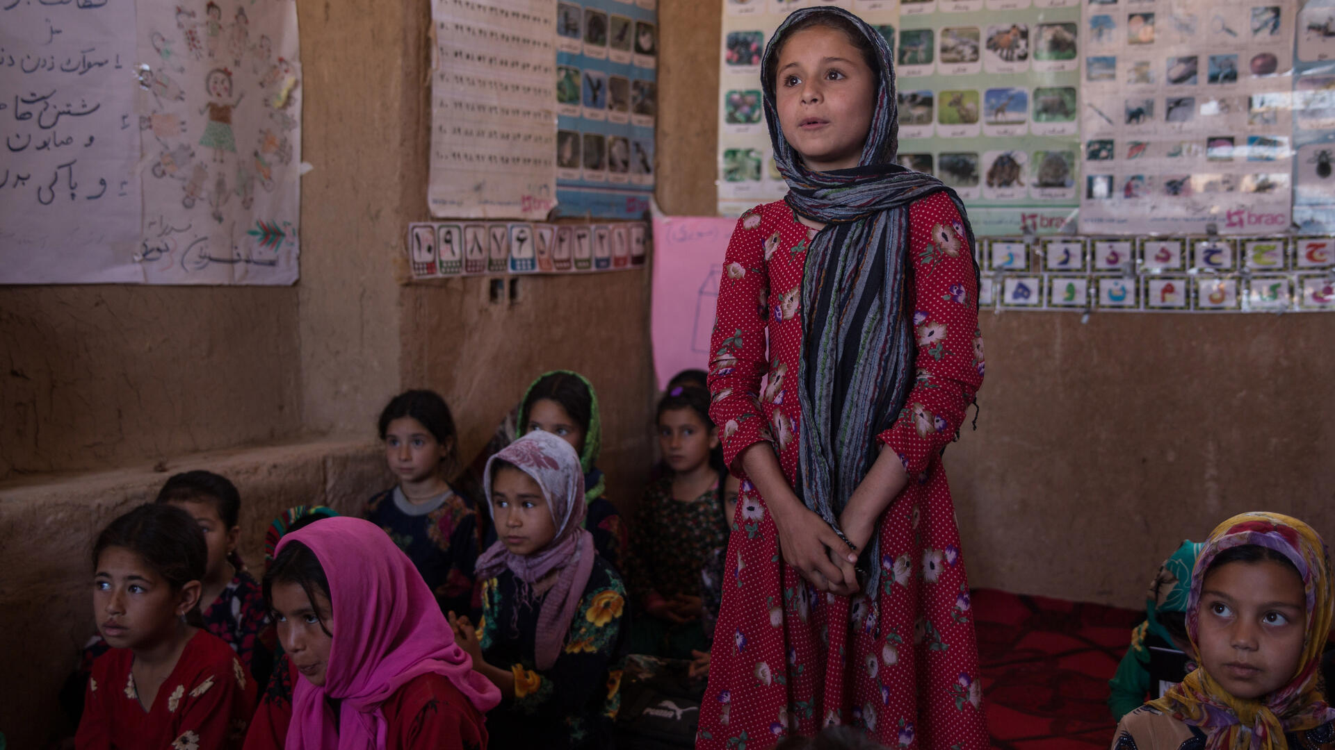A young girl stands to speak, hands clasped, in a classroom in Afghanistan.