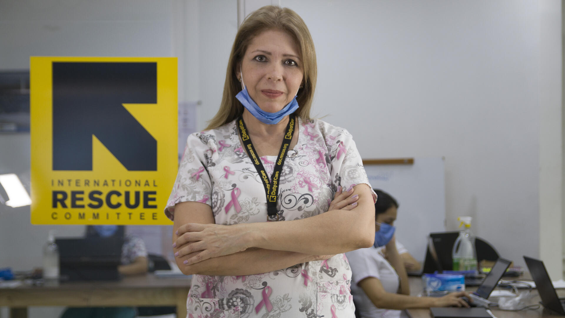 Dr. Edna Patricia Gomez stands in scrubs with her arms crossed. She has mask at her chin and there is an IRC logo behind her.
