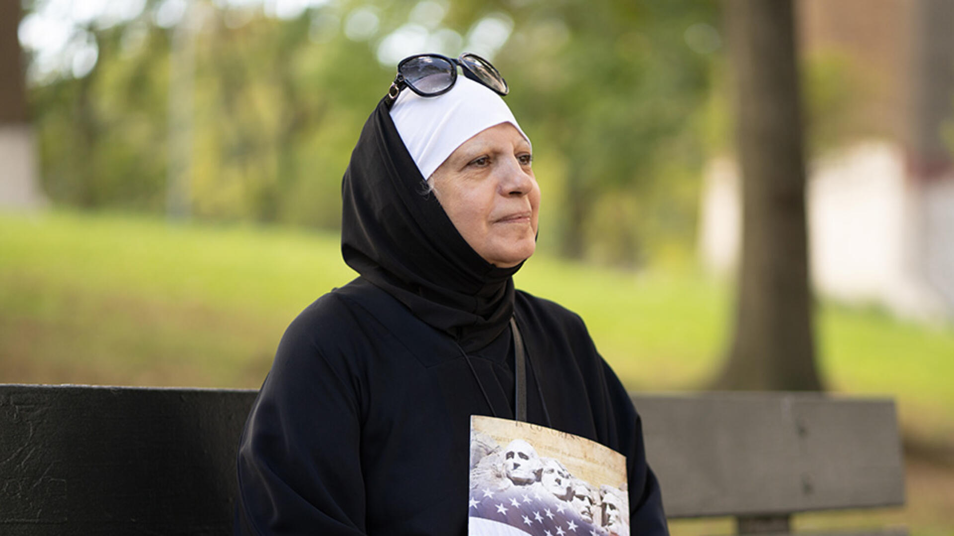 Maha al-Obaidi sits on a park bench looking off into the distance and holding a U.S. citizenship test study book.