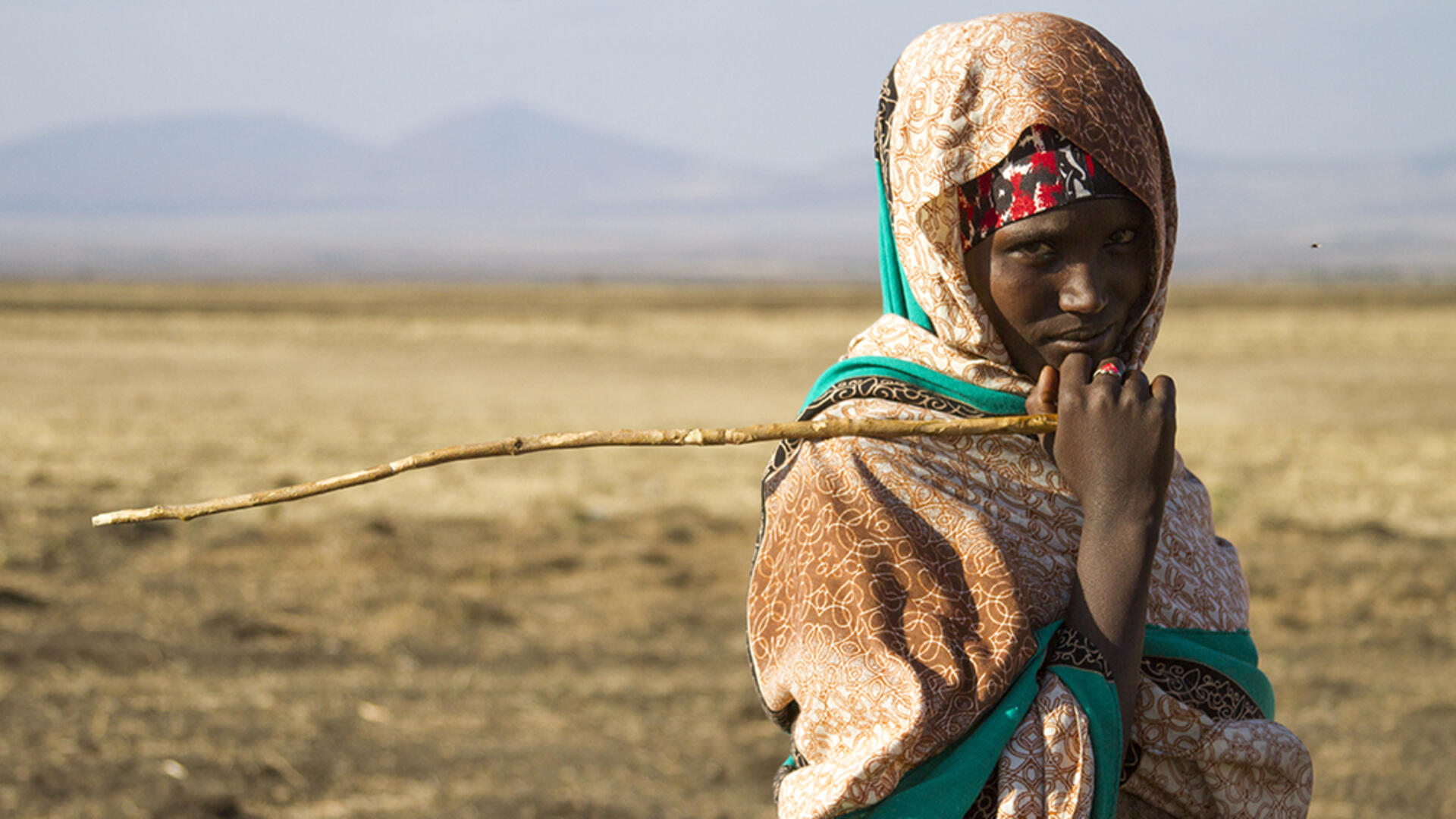 A teenage girl, holding a stick and looking at the camera, stands in a drought affected very dry landscape with mountains in the distance.