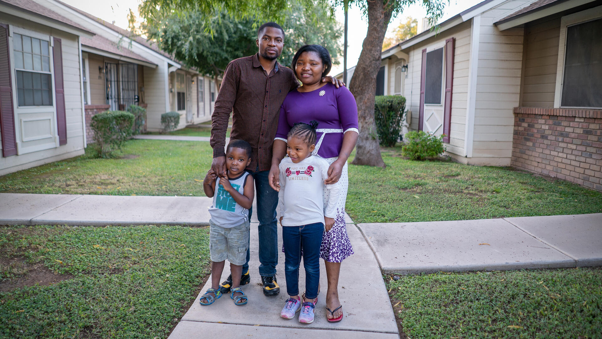 Robert, Edith and their young daughter and son stand for a photo on the sidewalk outside their home in Arizona
