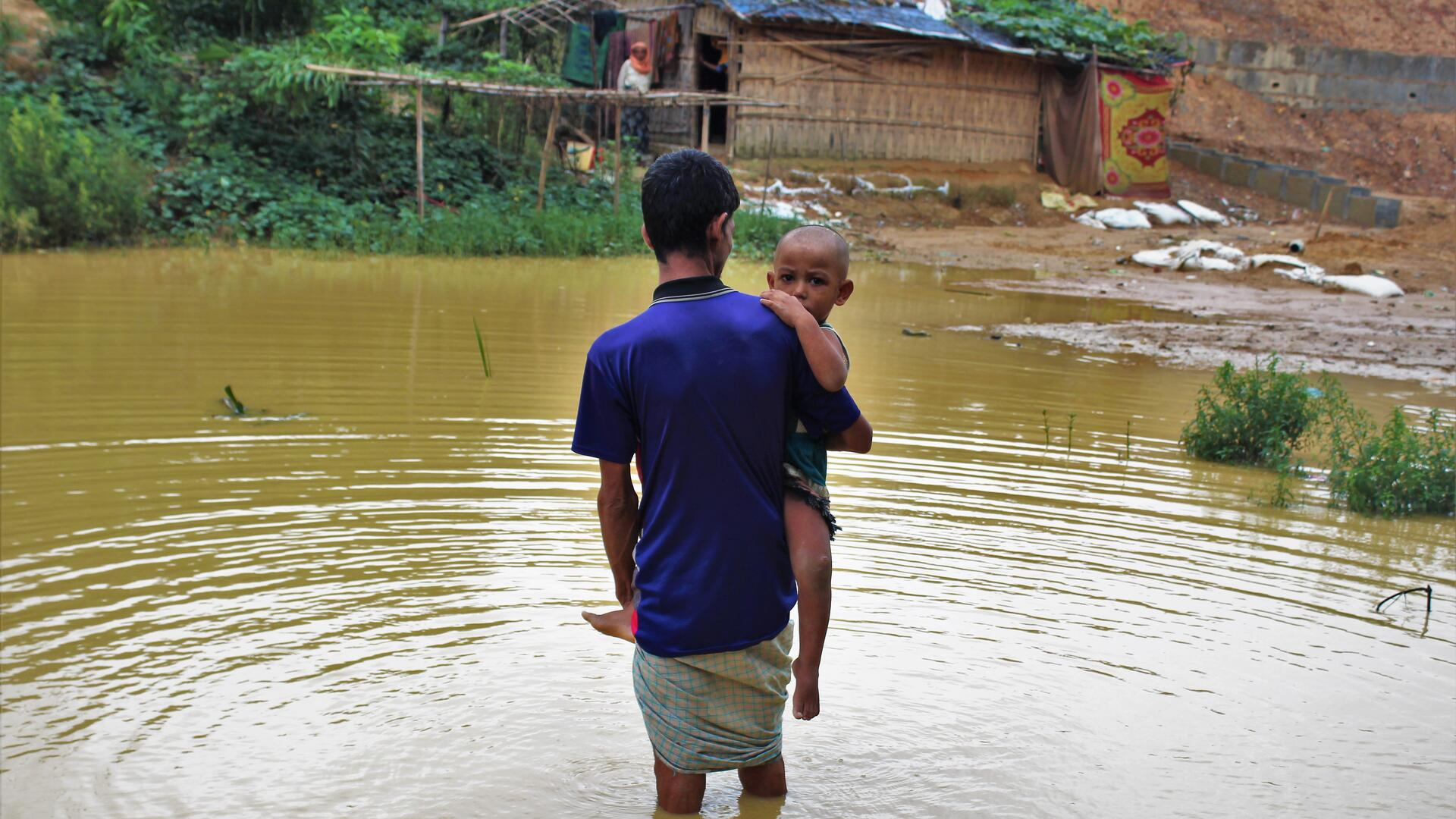 A Rohingya refugee man from Myanmar carries his two-year-old son through nearly knee-deep flood waters in a refugee camp in Bangladesh.