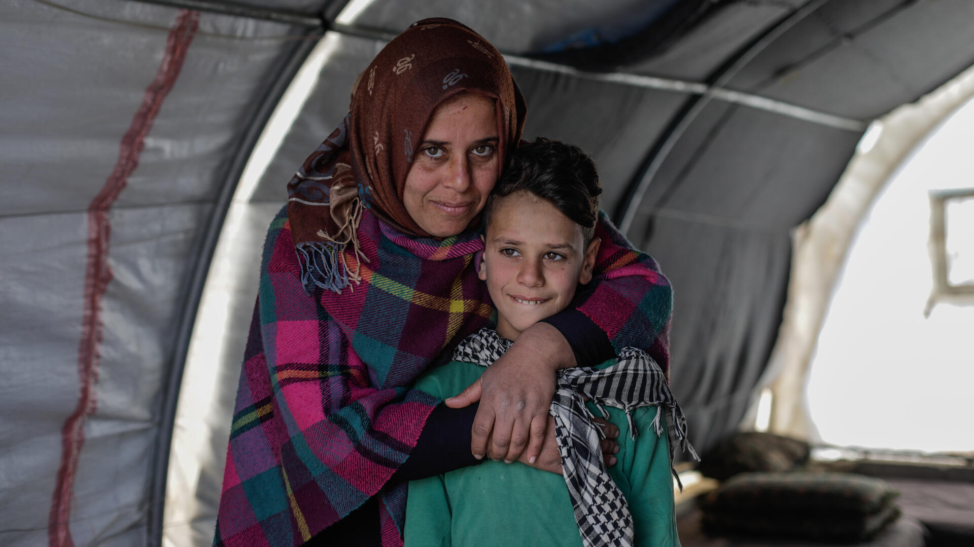 Sundus hugs her son Omar while standing behind him in a tent. Both are smiling and looking at the camera.