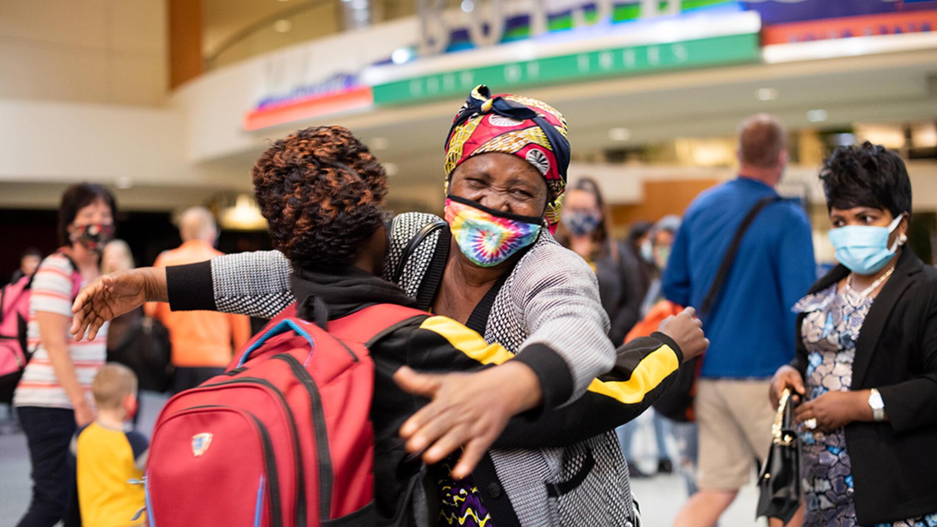 Wanyema Mitambo, wearing a mask, hugs her grandchild in the Boise Airport