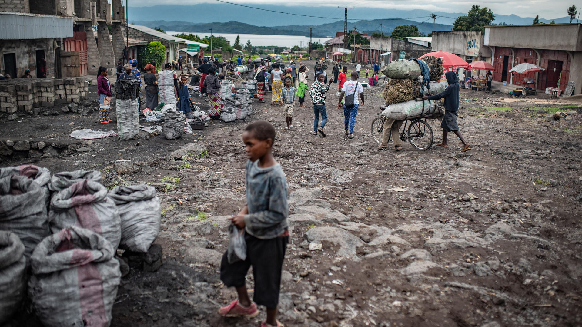 A young boy and other people on the street in Goma, DRC on a cloudy day