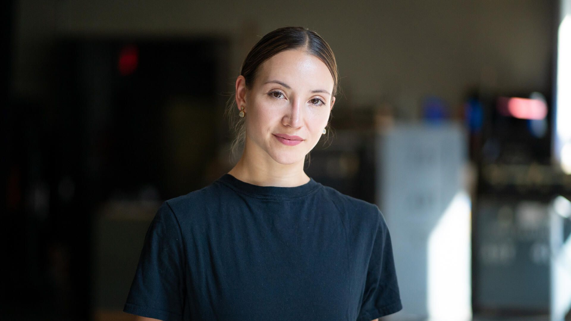 With her hair pulled back and wearing a black t-shirt, Christine Shevchenko looks at the camera for a World Refugee Day 2021 photo shoot,