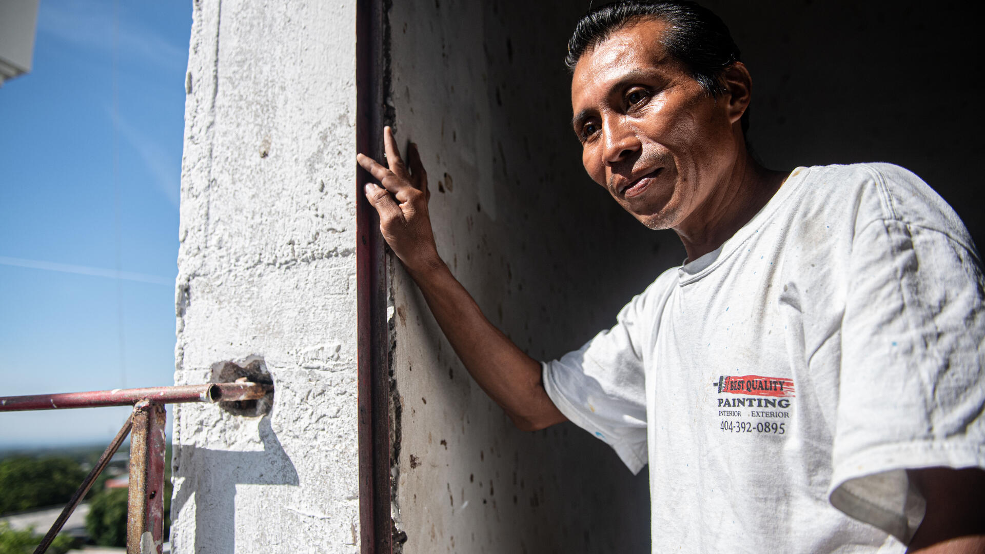 Reynaldo, a Salvadoran man who works as a painter, stands in the doorway of a church in El Salvador.