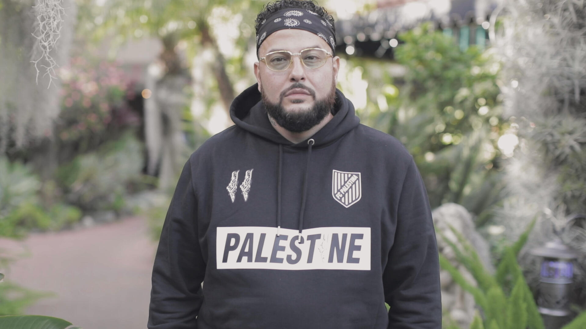 """Rapper, songwriter and record producer Belly stands outside wearing a headband and sweatshirt with the text """"Palestine"""" for a World Refugee Day 2021 photo shoot."""