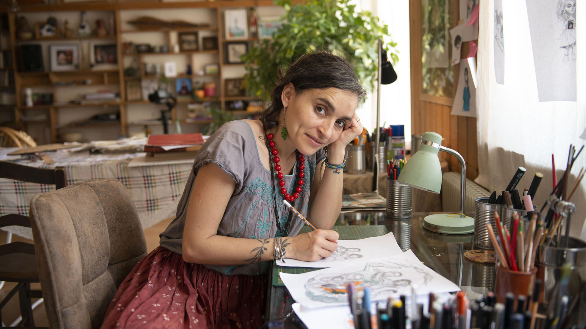 Artist and activist Diala Brisly, leaning on her desk holding a pencil, sketches an illustration of refugees for World Refugee Day 2021.