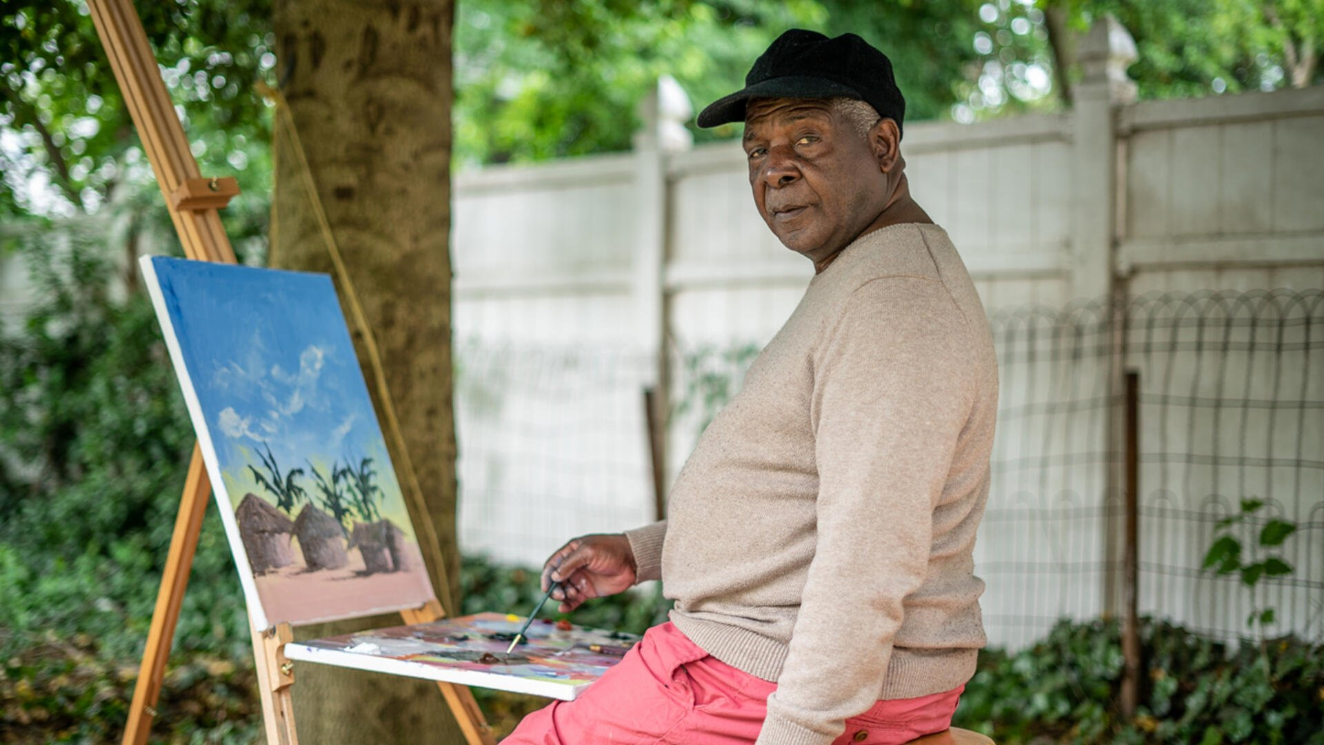 Congolese artist Muyambo Marcel Chishimbasite outside at his easel painting a landscape