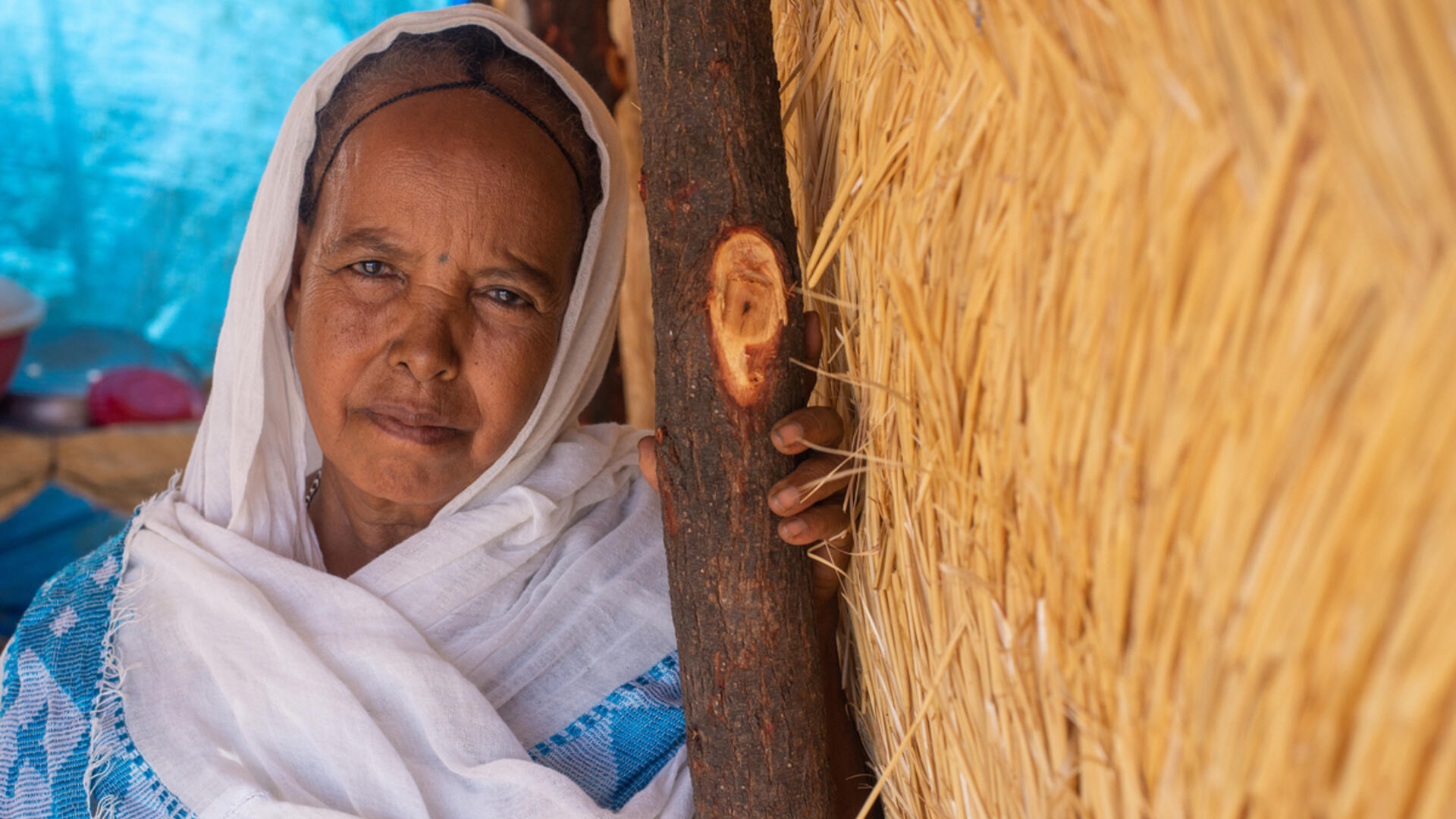60-year old Berhan leans against a wooden beam supporting a thatched shelter where she lives in Sudan.