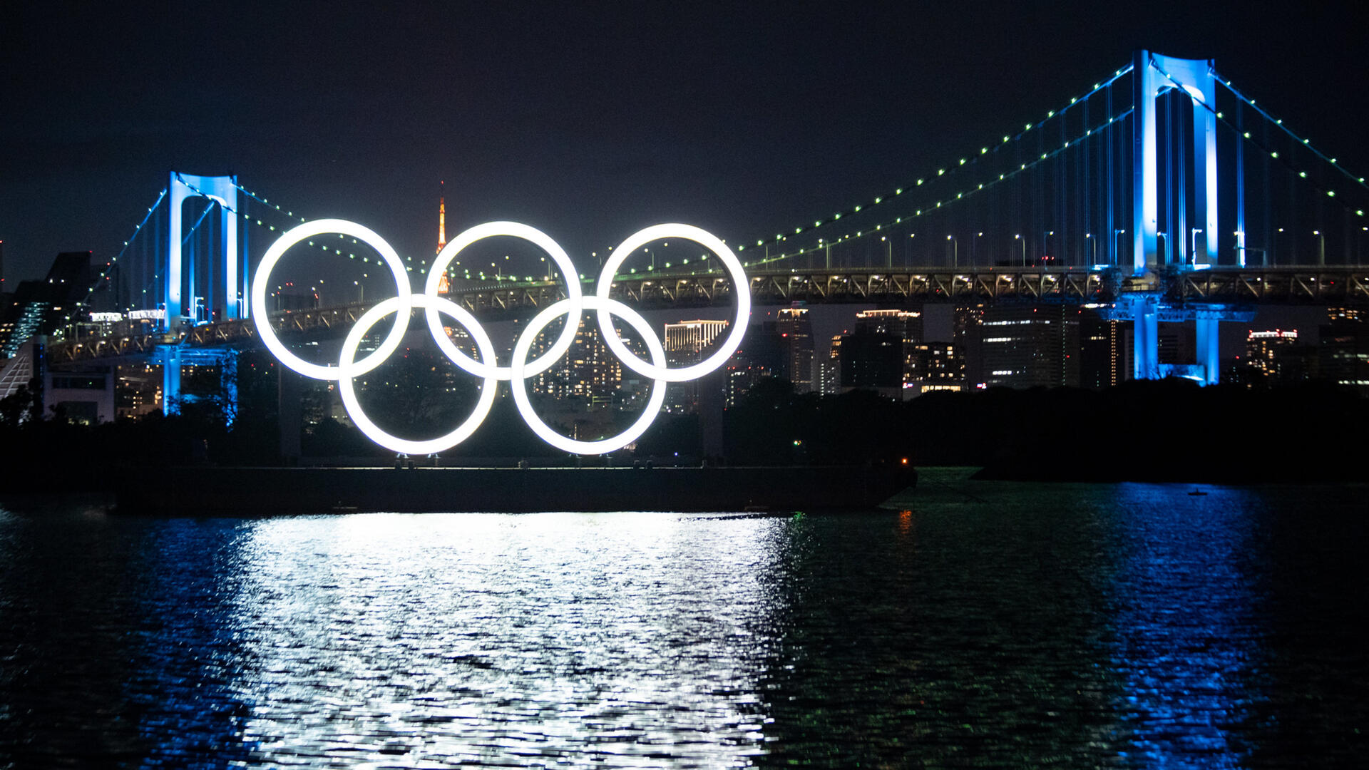 Night view of illumiated Monument of Olympic Rings, set on a barge in Tokyo with a bridge behind it