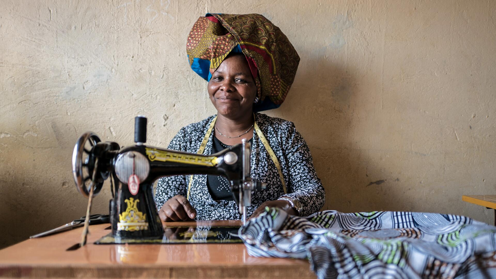 Domitila Kaliya, a Congolese refugee, smiles as she sits at her sewing machine