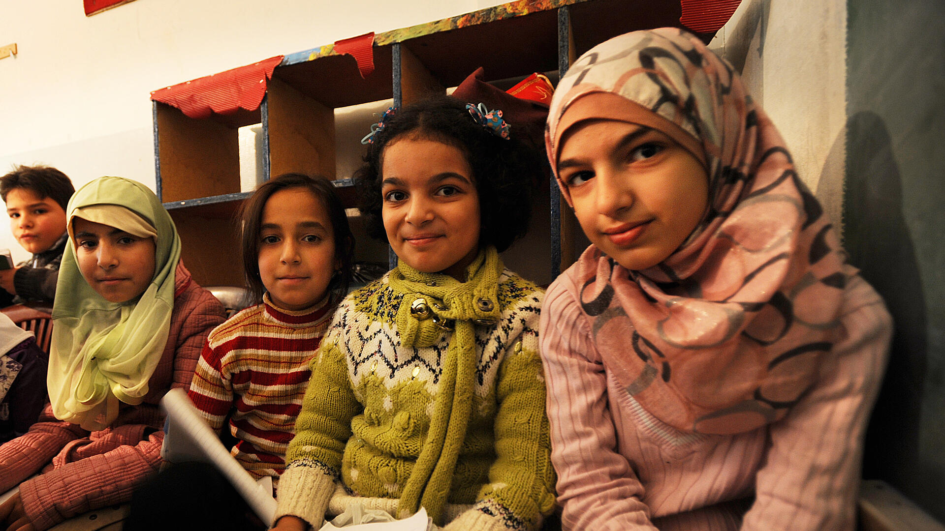 Four young Syrian girls sit in a makeshift school in Berkayel, Lebanon.