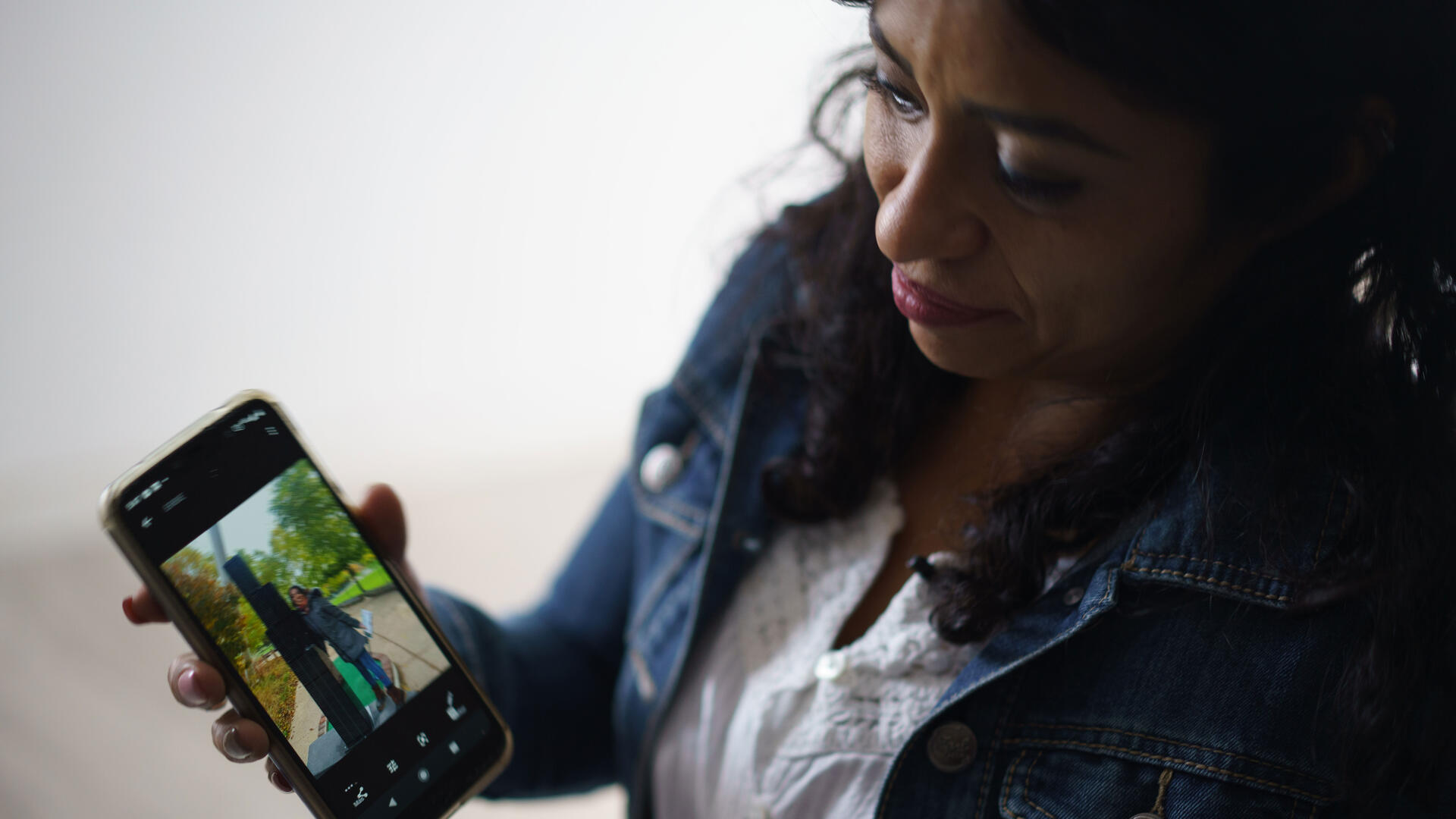 Rosa, wearing a jean jacket, holds an smart phone to show a photo of her daughter, Emily.