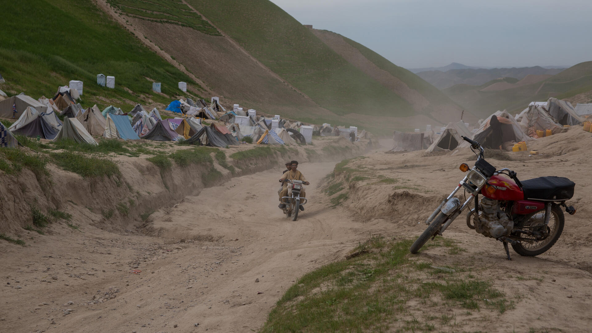 A camp for drought displaced people in Afghanistan. there is a motorcycle in the foreground as well as two men on a motorcycle on the road, and tents in the background on a mountainous landscape.
